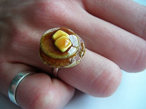 Miniature food pancake ring, complete with creamy pats of butter and golden delicious maple syrup